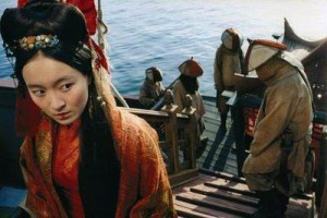 A still from Singing Behind Screens. The character of Ching Shih wears a red robe and an elaborate Chinese hairstyle. She glances behind her, to other sailors on her ship, dressed very plainly.