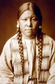 A sepia-toned photograph of a Native American woman. She wears a loose shirt and a thick string of bone pipe beads as a mantle. She has long hair, put into two braids and silver medallion earrings