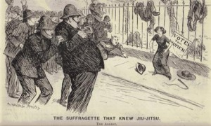 A Victorian cartoon. A woman stands against a fence, with several unconscious police officers draped over it. More police officers balk at arresting her. The woman has a belligerent demeanor.