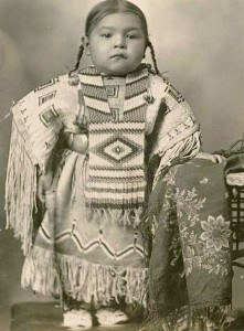 A black and white photograph of a small Native American girl. She has her long hair in two braids, and wears a decorated buckskin dress and large beaded necklace. A quilted object rests next to her.