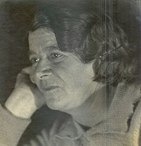 A black and white photo. A woman with short brown hair rests her face on her hands.