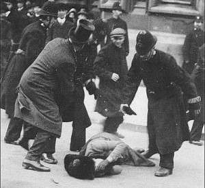 A black and white photo. A woman in Edwardina clothes lies (possibly unconscious) in the middle of the street. Several men and police offers are bent over her.