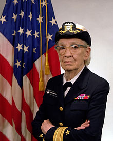 An older woman in Naval dress blues and a white captain's cap. She stands with her arms crossed, an American flag behind her.