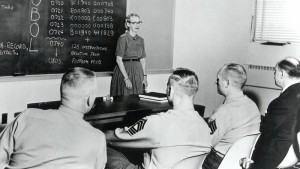 A black and white photo. A woman stands next to a chalkboard, instructing a group of men in military uniforms.