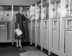 A black and white photo. A woman, wearing a 1950s style dress, holds some papers while looking at a bank of large computers.