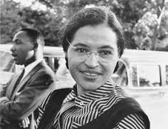 A young black woman in a black and white photograph. She wears glasses, and has a black and white striped shirt underneath a dark vest.