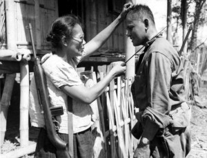 A Huk woman shows an American GI how it's done.